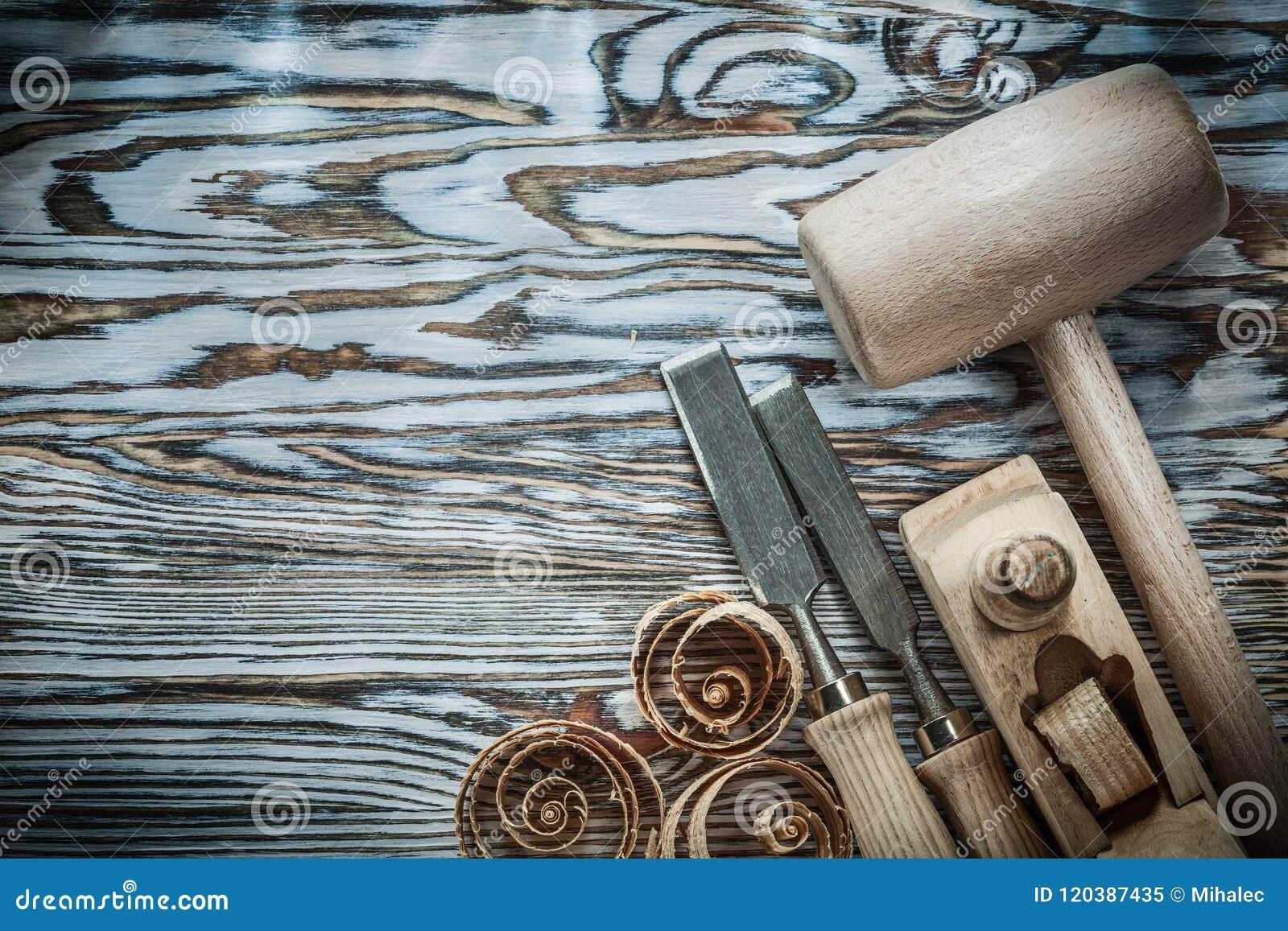 Considere aparas ondulados plaina dos formões do martelo na placa de madeira