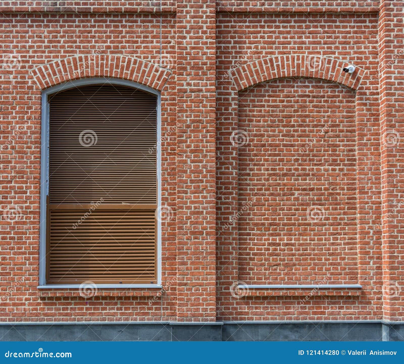 A construção é feita do tijolo no estilo do sótão A janela com cortinas e uma janela colocaram com tijolo
