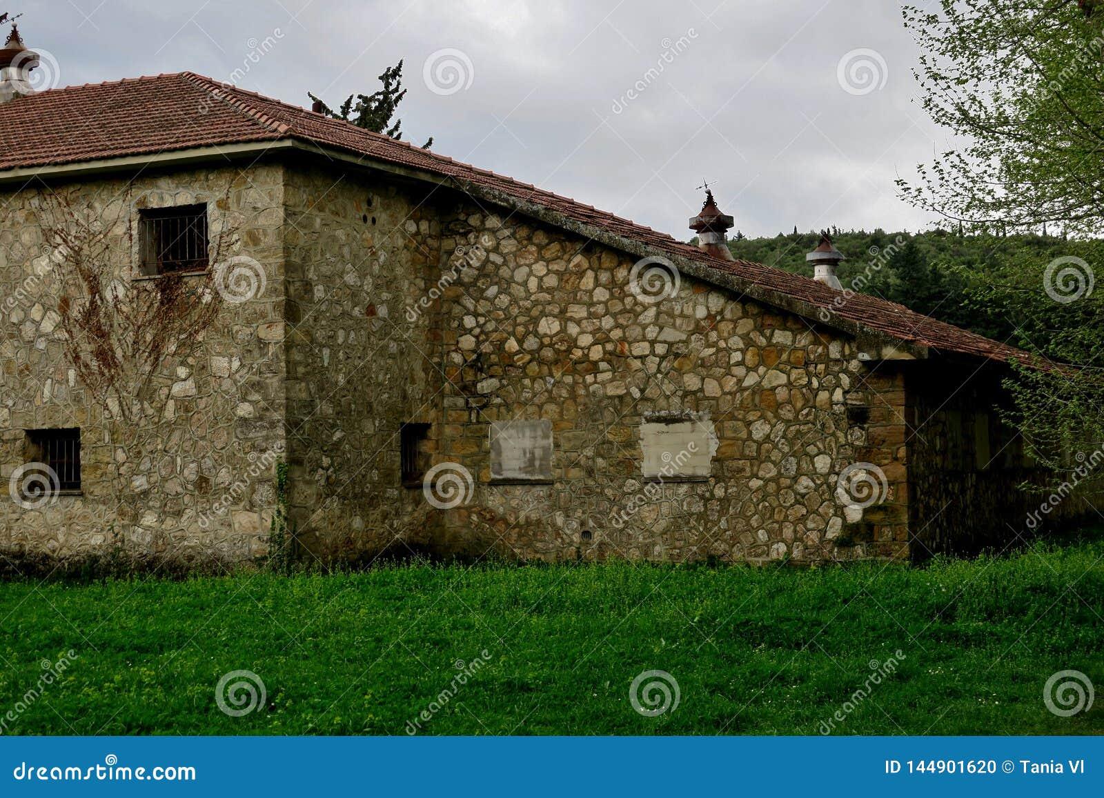Construção abandonada velha em um gramado verde no meio da floresta