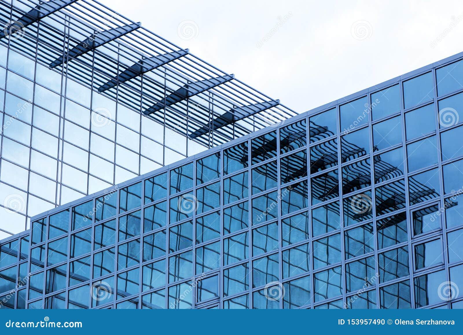 Construção do negócio com exterior de vidro moderno no fundo do céu azul