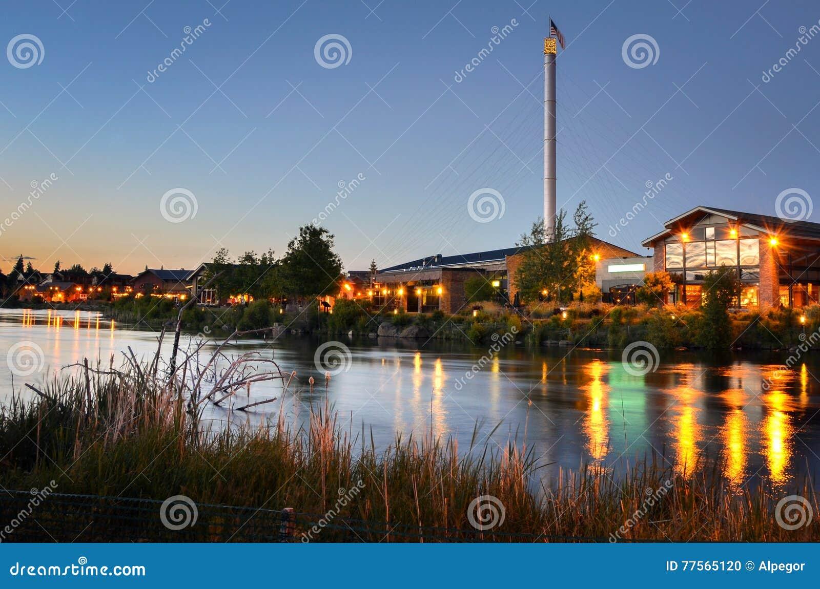 Construções renovadas ao lado de um rio no crepúsculo