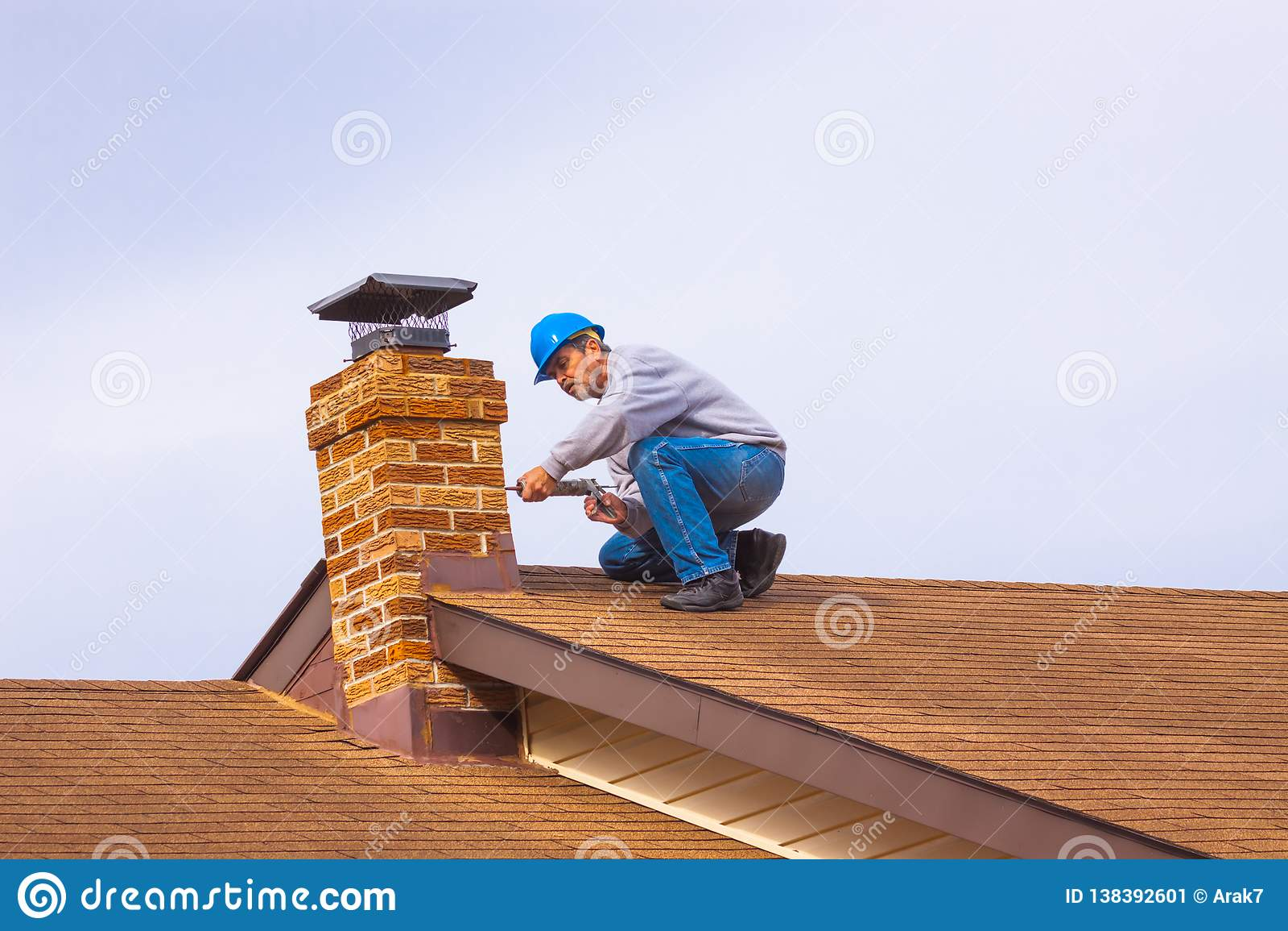 Constructeur d entrepreneur sur le toit avec la cheminée bleue de calfeutrage de masque