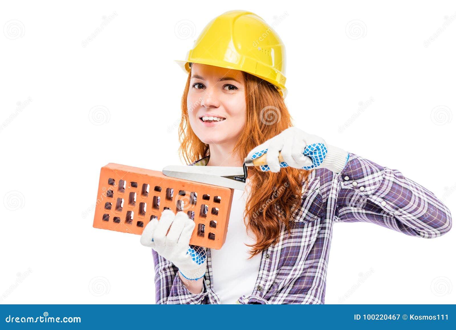 Constructeur de femme avec une brique dans un casque antichoc jaune contre un blanc