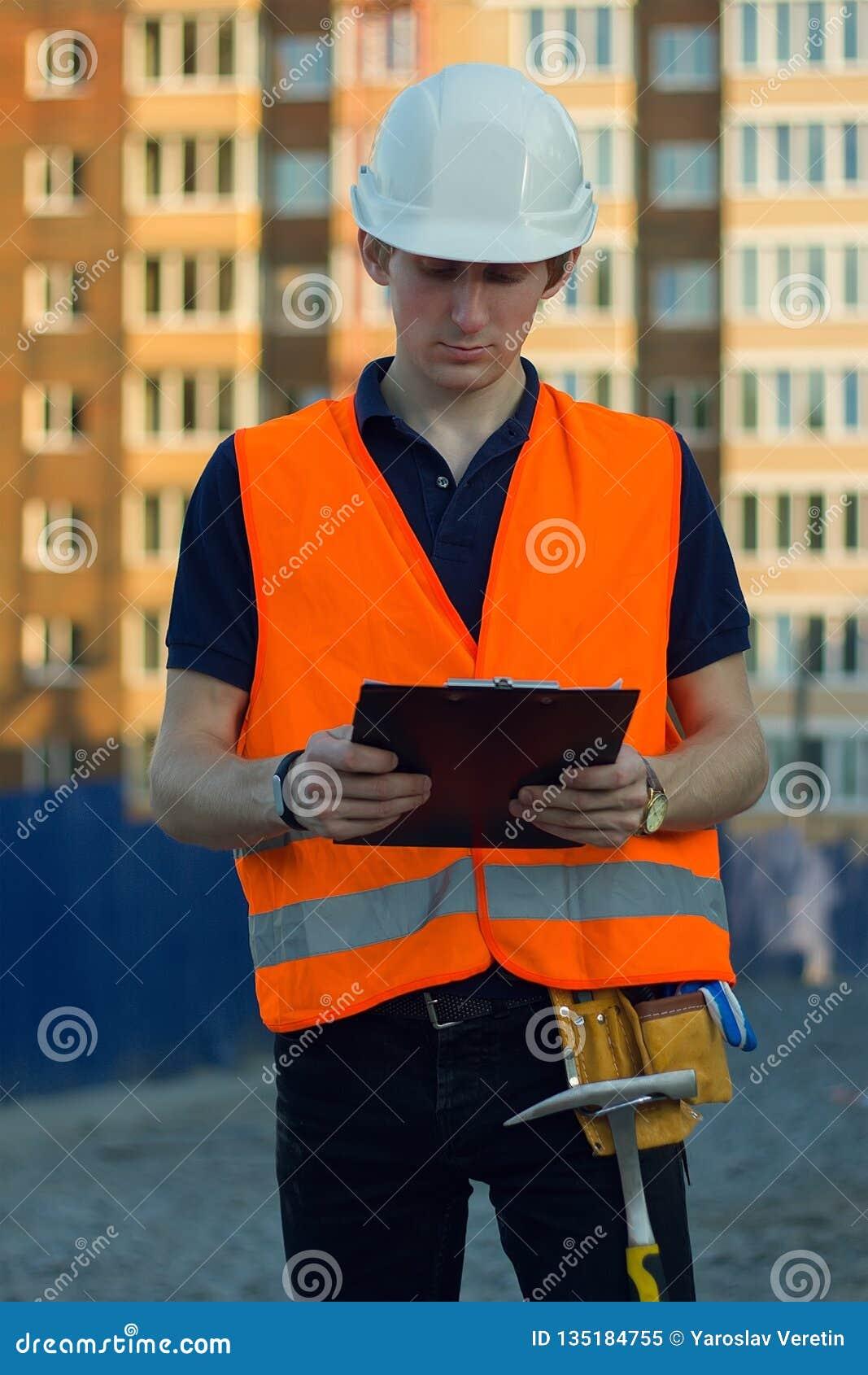 Constructeur réfléchi dans le gilet réfléchissant et casque regardant le modèle