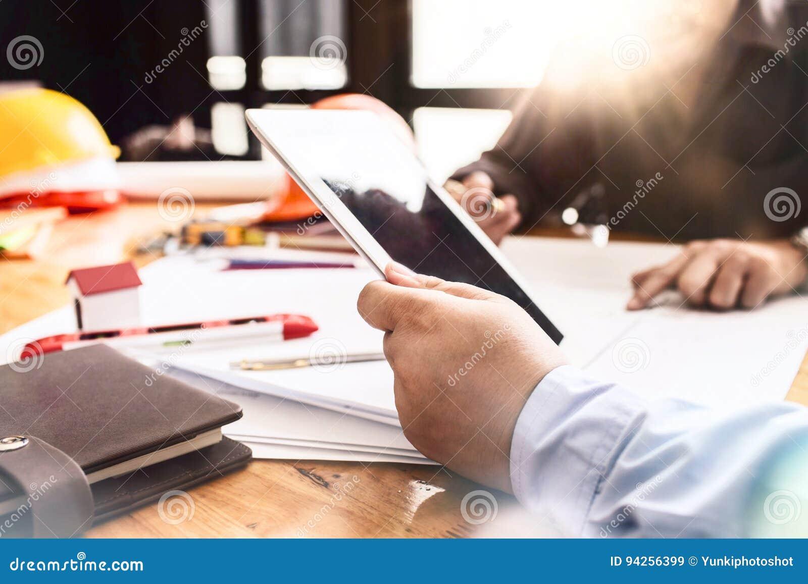 Constructiewerkzaamhedenvergadering op werkplaatskantoor die har werken
