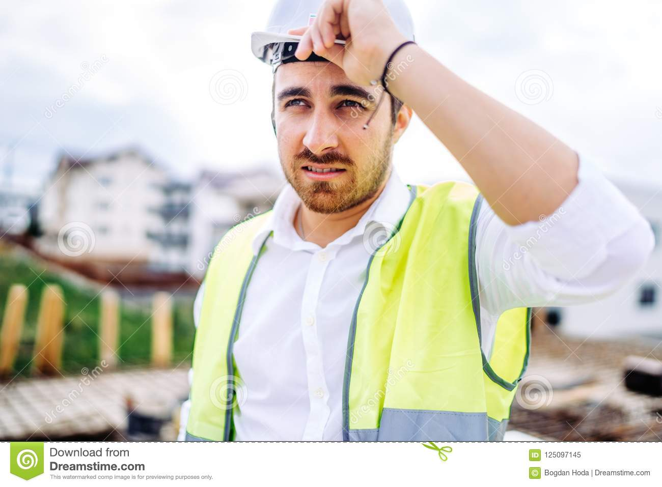 architect working on construction site, wearing hard hat and safety vest