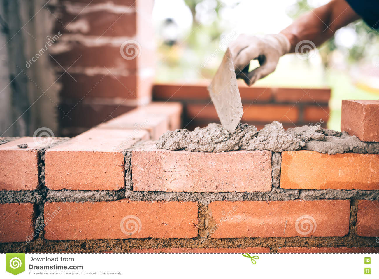 Construction bricklayer worker building walls with bricks, mortar and putty knife