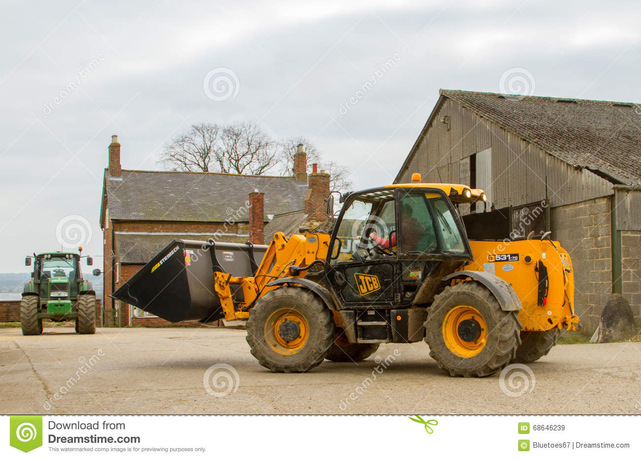 construction digger loader in farm yard with barn editorial stock