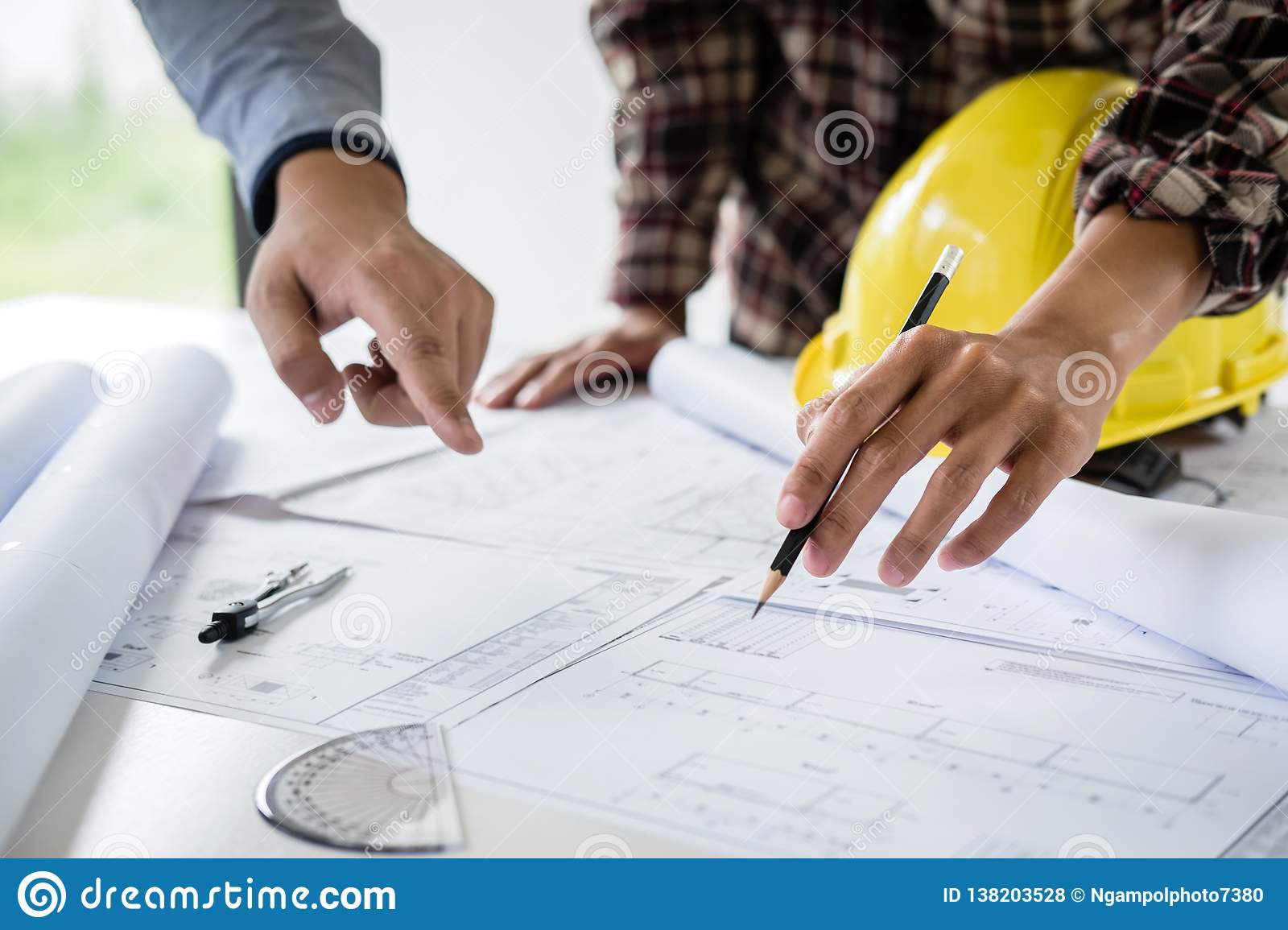 Construction engineering or architect discuss a blueprint while checking information on drawing and sketching meeting for