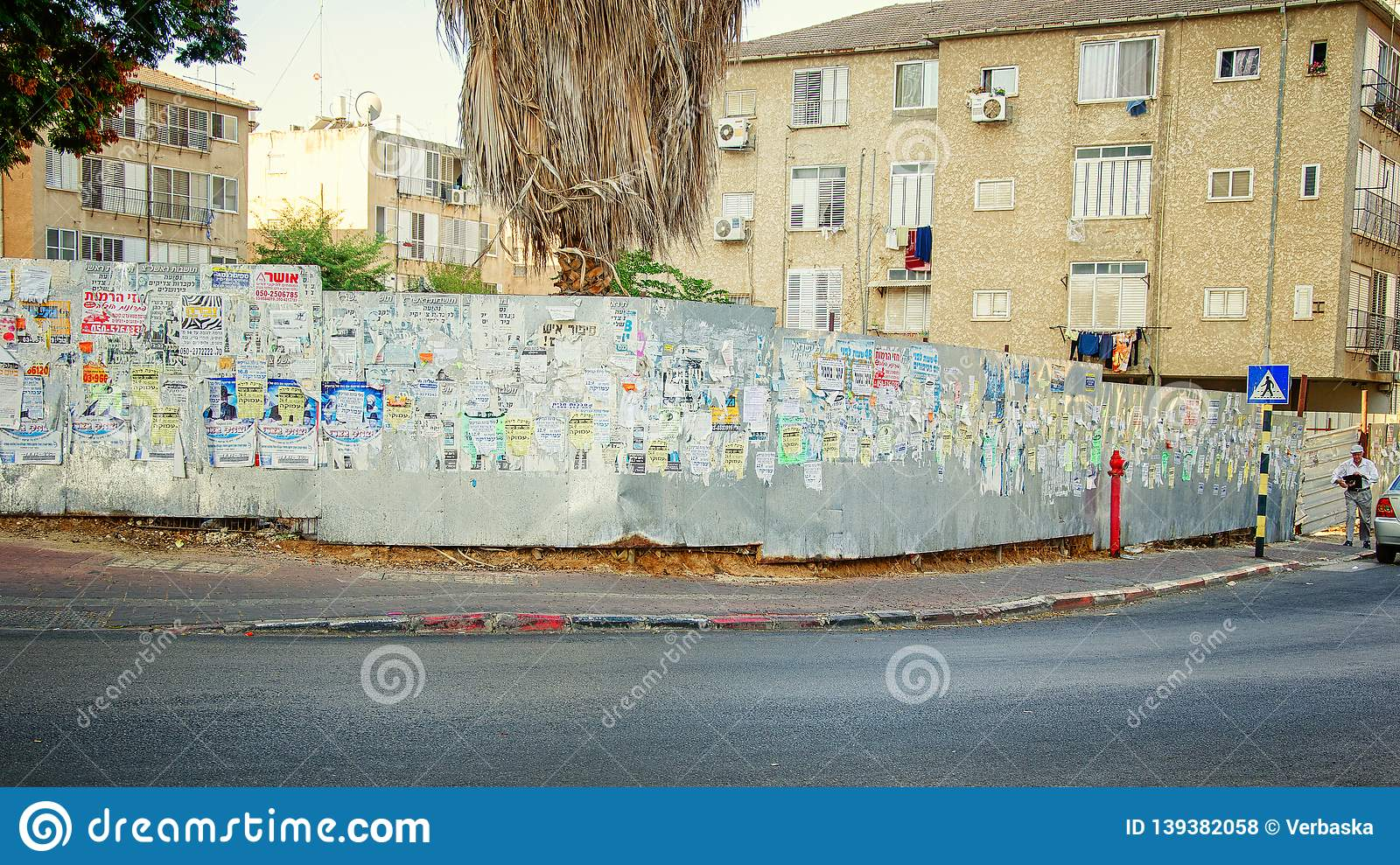 Personal advertisements and posters cover a metal fence