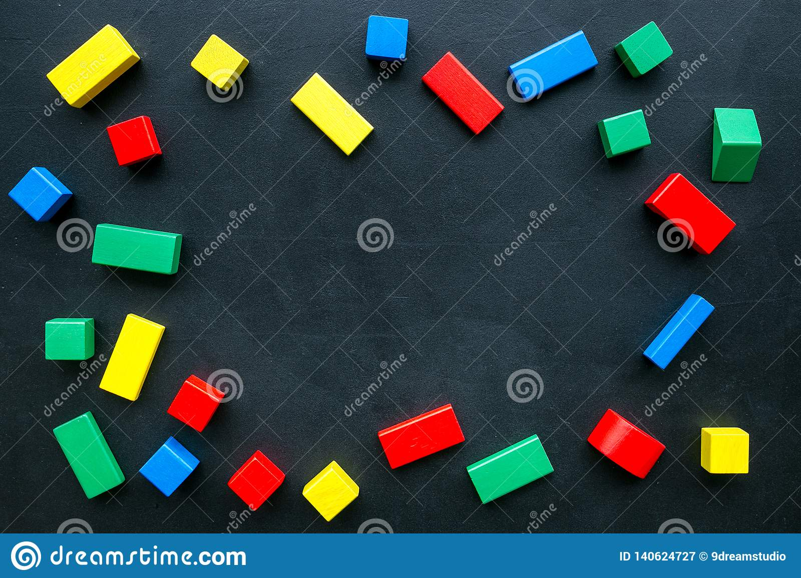 Construction game for kids. Wooden building blocks, toy bricks on black background top view space for text frame