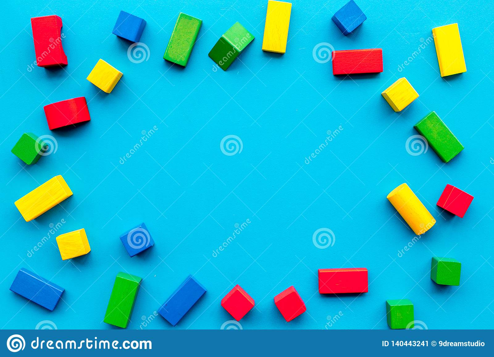 Construction game for kids. Wooden building blocks, toy bricks on blue background top view copy space frame