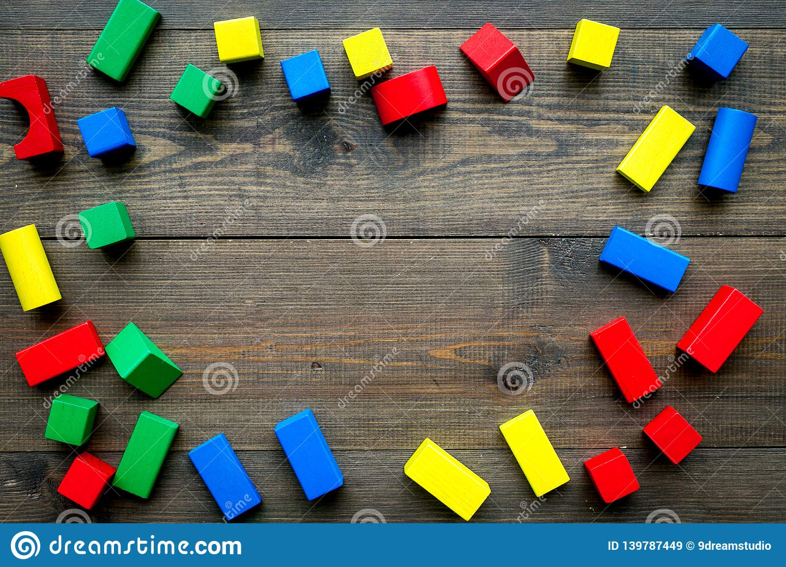 Construction game for kids. Wooden building blocks, toy bricks on dark wooden background top view space for text frame