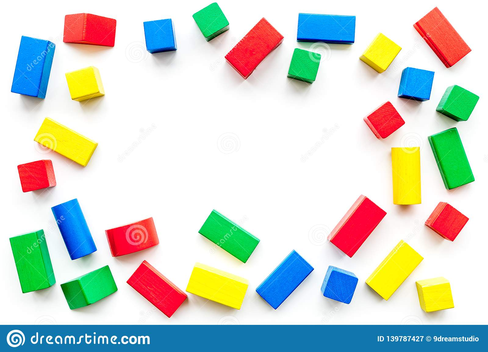 Construction game for kids. Wooden building blocks, toy bricks on white background top view copy space frame