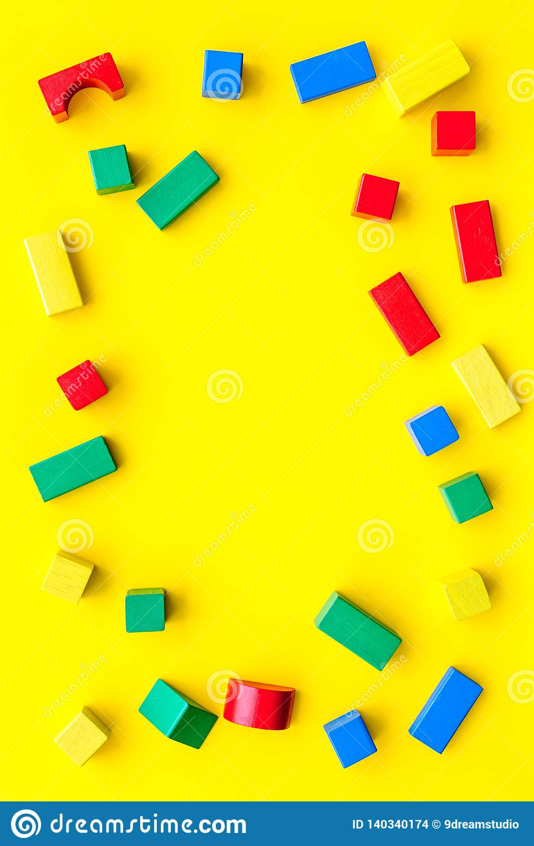 Construction game for kids. Wooden building blocks, toy bricks on yellow background top view space for text frame
