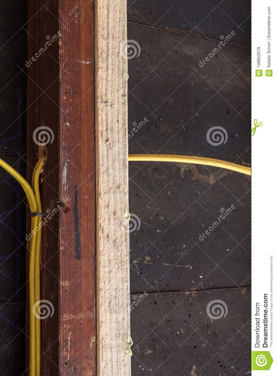 Construction renovation detail of old wall stud and new sistered stud with  yellow electrical wiring and