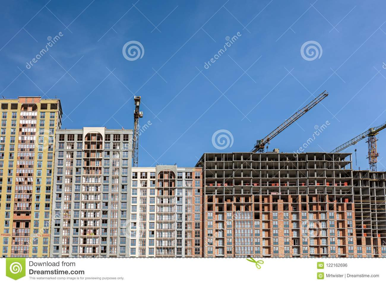 Construction of residential building. yellow cranes against blue