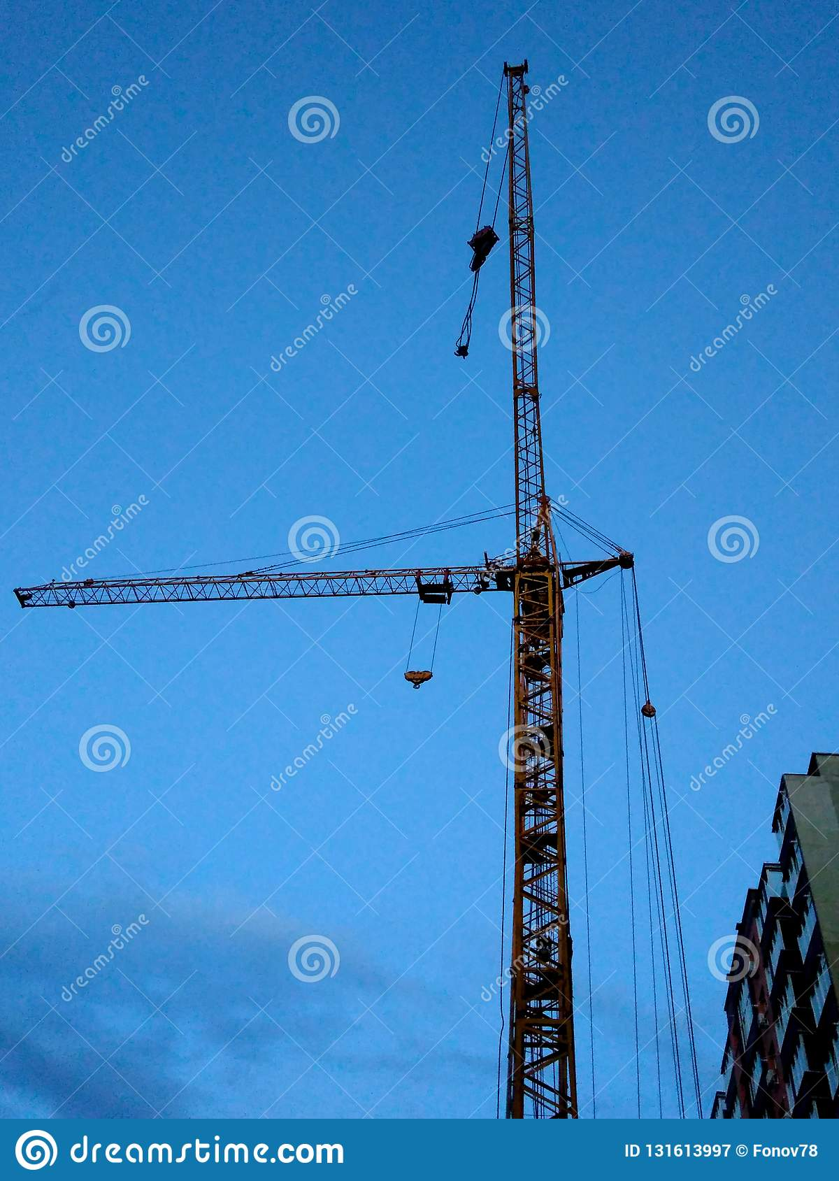 Construction site with a crane, repair work, blue sky at sunset