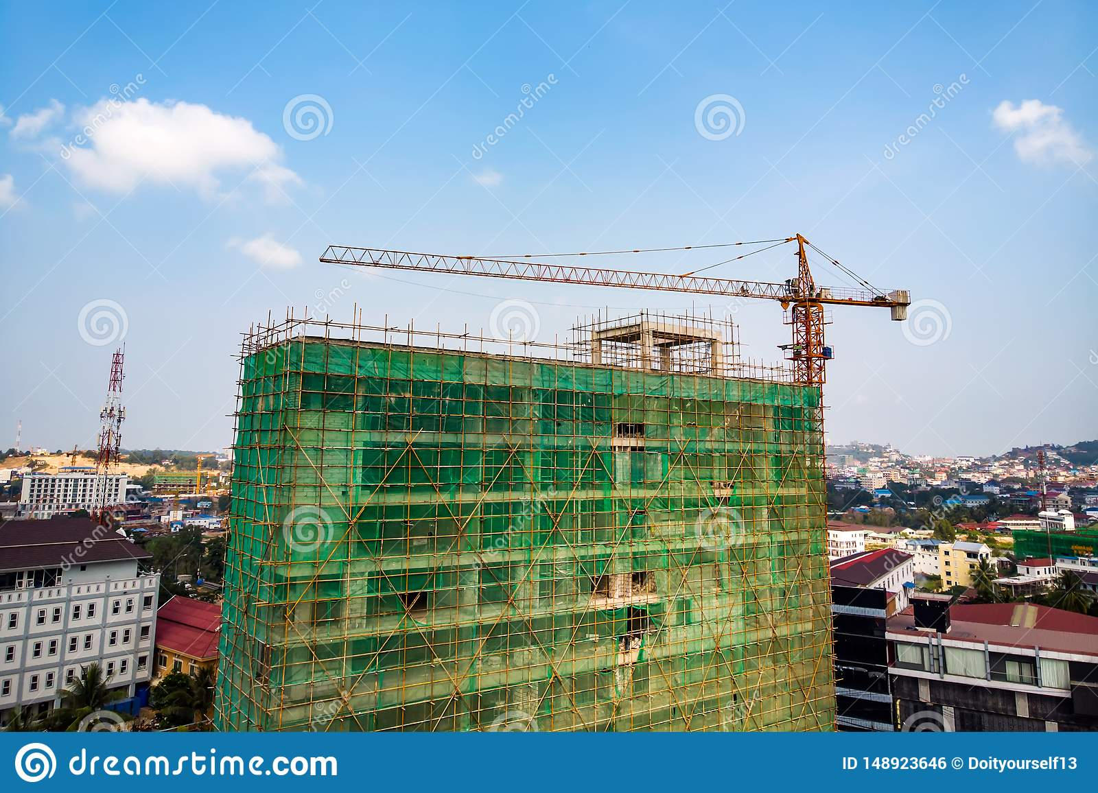Construction site next to modern office, residential building. Working crane and safety net with cloud blue sky . Green grid