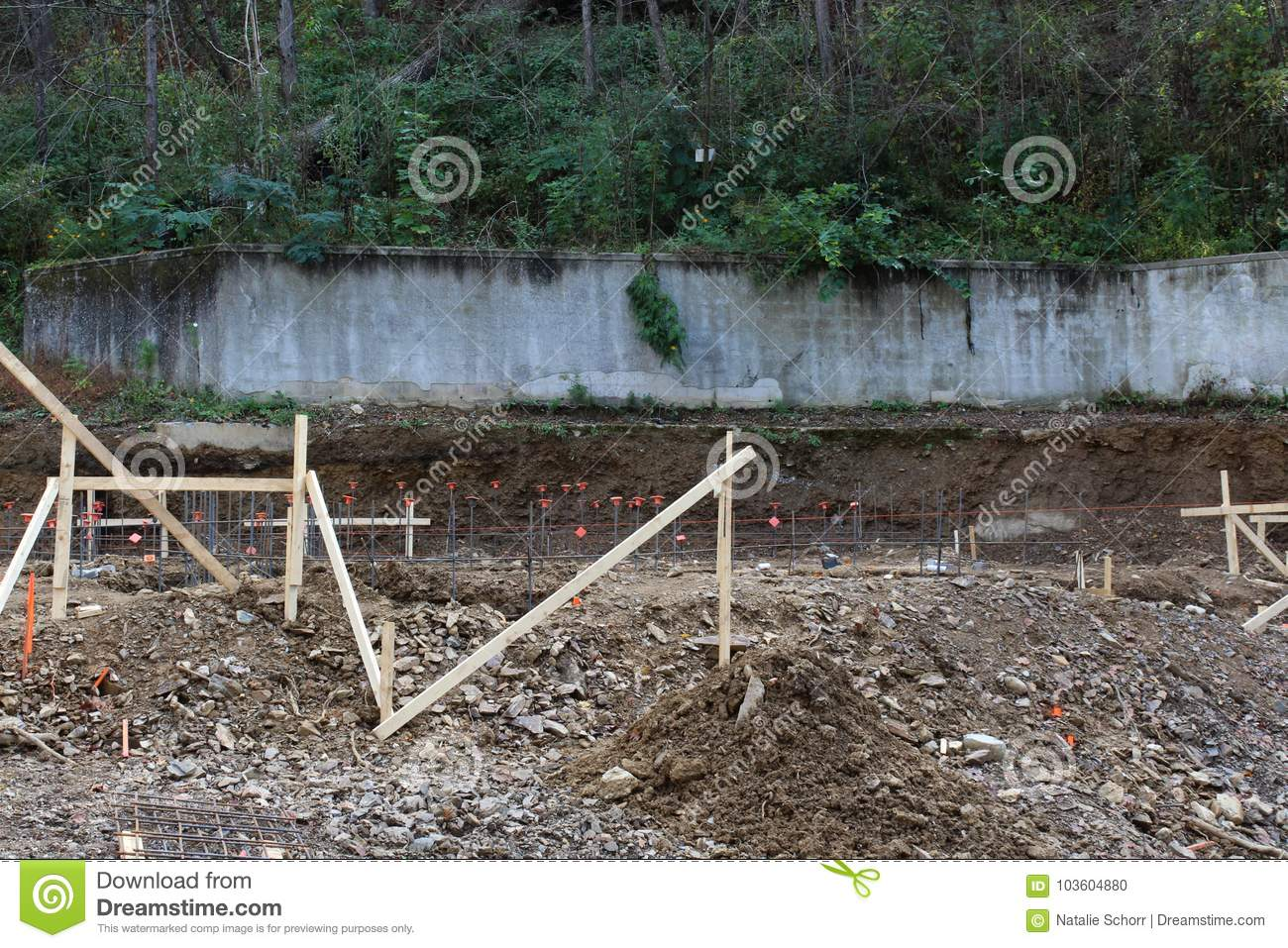 Construction site view of concrete retaining wall on hillside behind dug footings and rebar