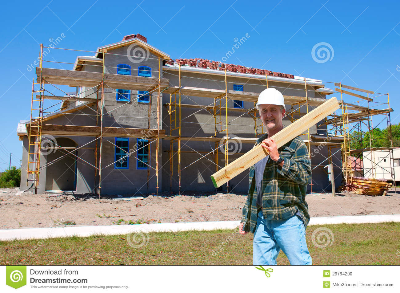 House construction with a contractor at work stock photo for Building under construction insurance