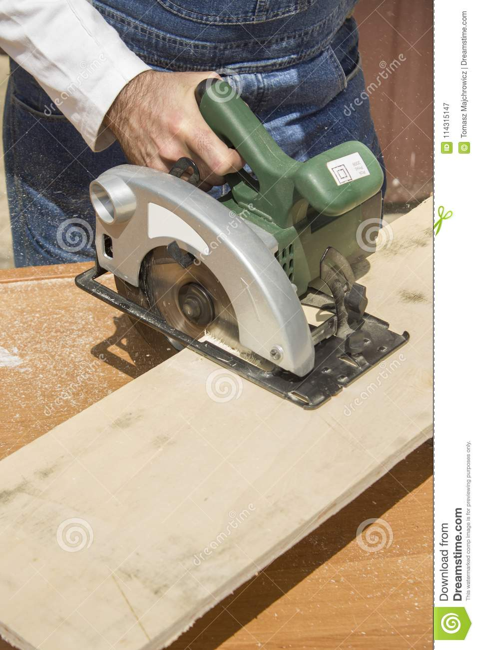 Construction worker crosses a board with a circular saw. The carpenter cuts  the board with a manual electric saw.