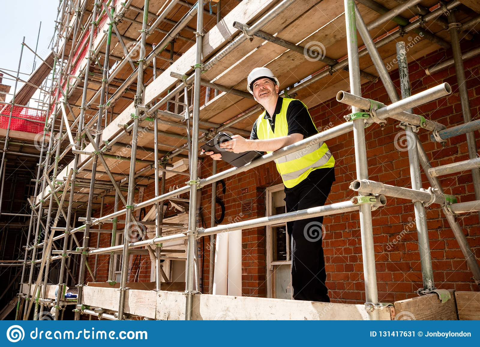 Construction worker, foreman or architect on scaffolding at construction site with clipboard