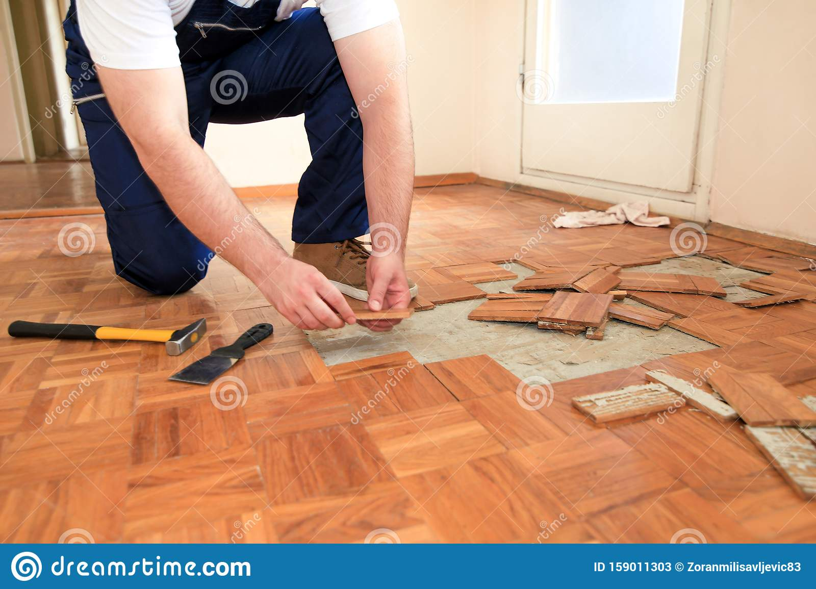 Construction Worker And Handyman Is Removing Old Wooden Parquet