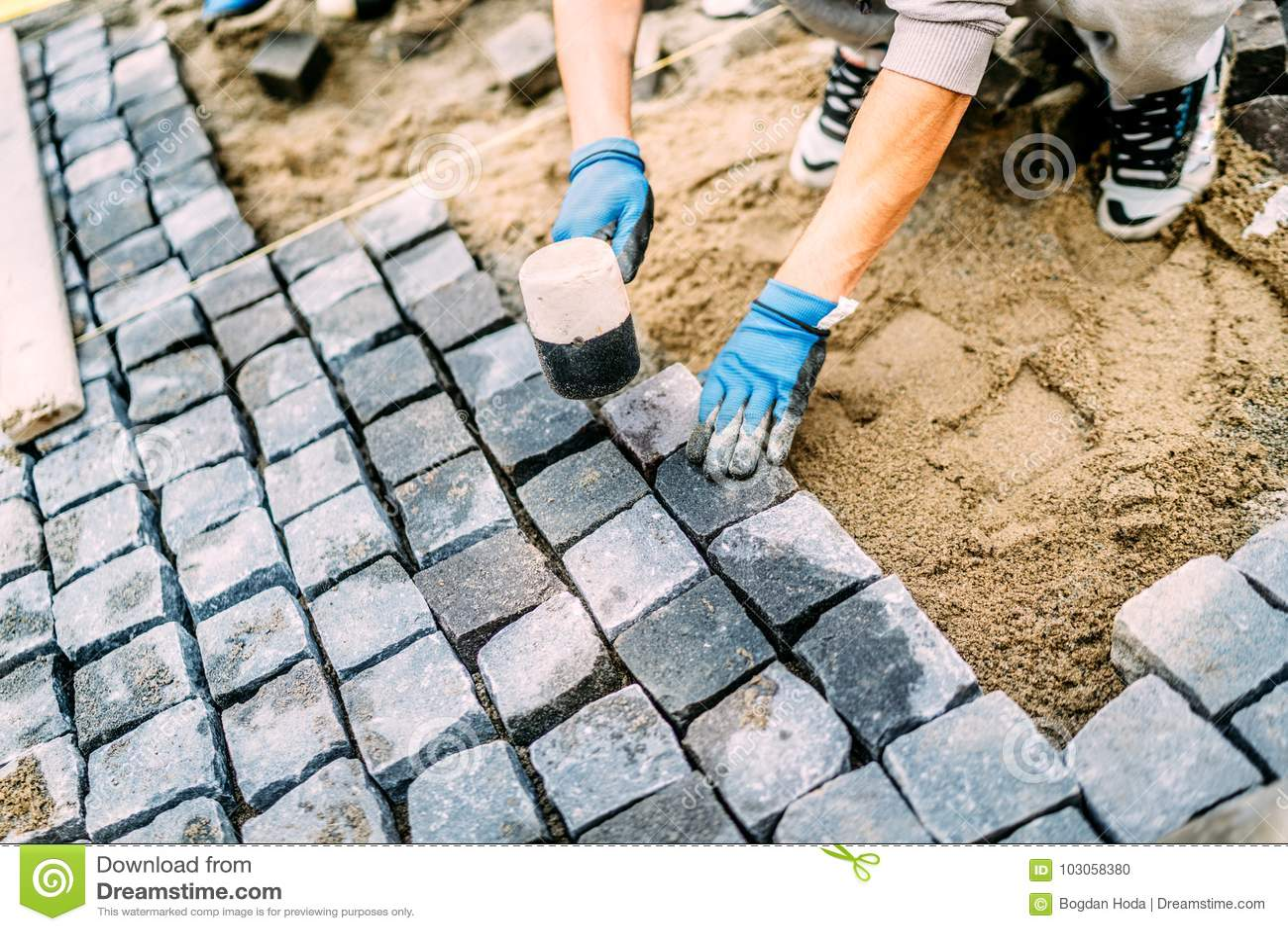 construction worker, handyman using cobblestone granite stones for creating walking path. Terrace or sidewalk details