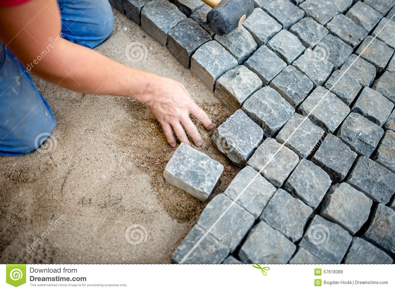 Construction Worker Laying Cobblestones And Stone Blocks
