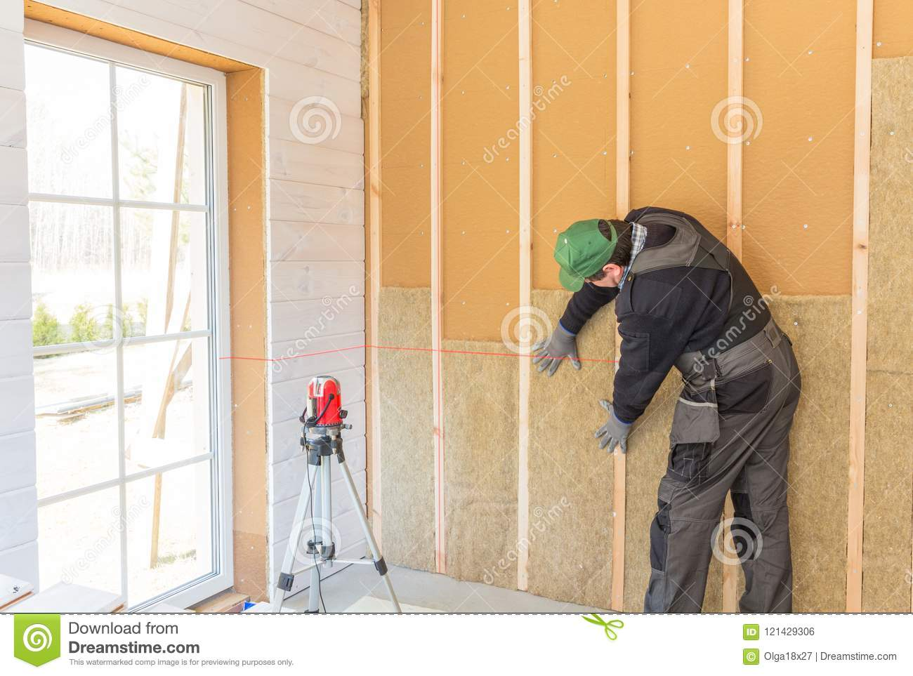 . The Worker Makes Finishing Works Of Walls With A White Wooden Board