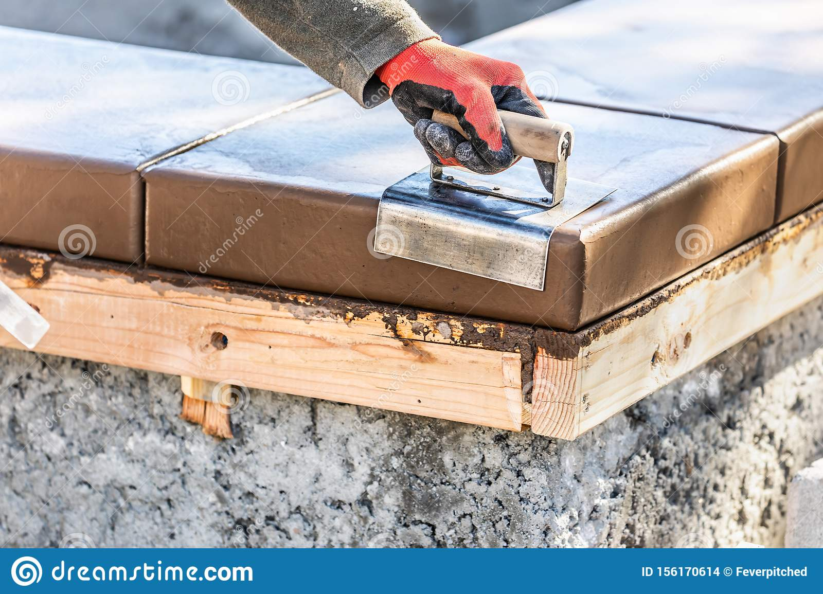 Construction Worker Using Stainless Steel Edger On Wet