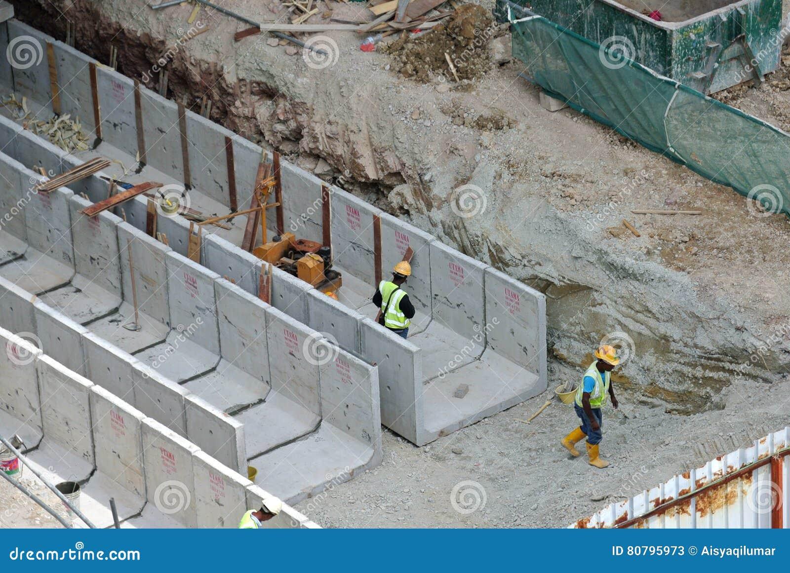 Construction Workers Installing Precast Concrete Drain