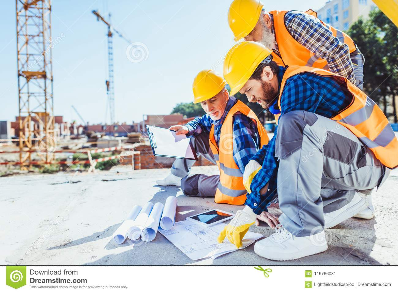 baf85b6c1ecce construction workers in uniform sitting on concrete at construction site