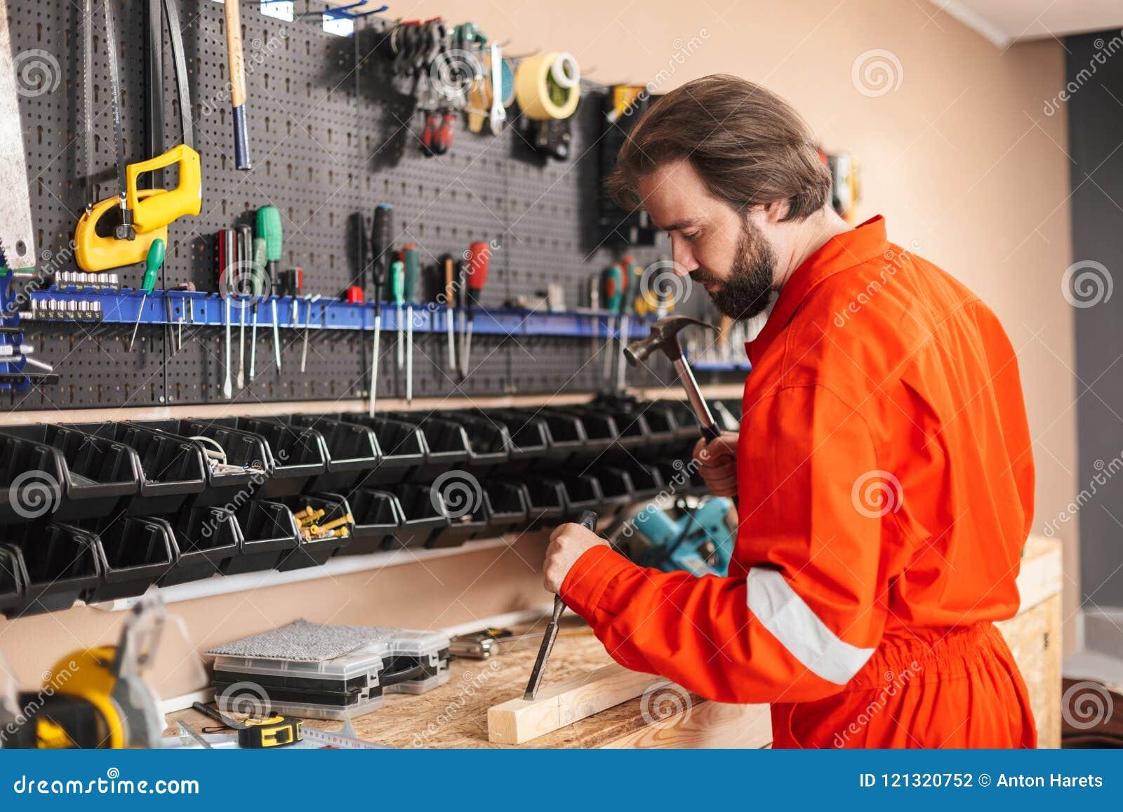 ba63e7a8086 Constructor en ropa de trabajo anaranjada usando el martillo con el soporte  de diversas herramientas cerca en taller