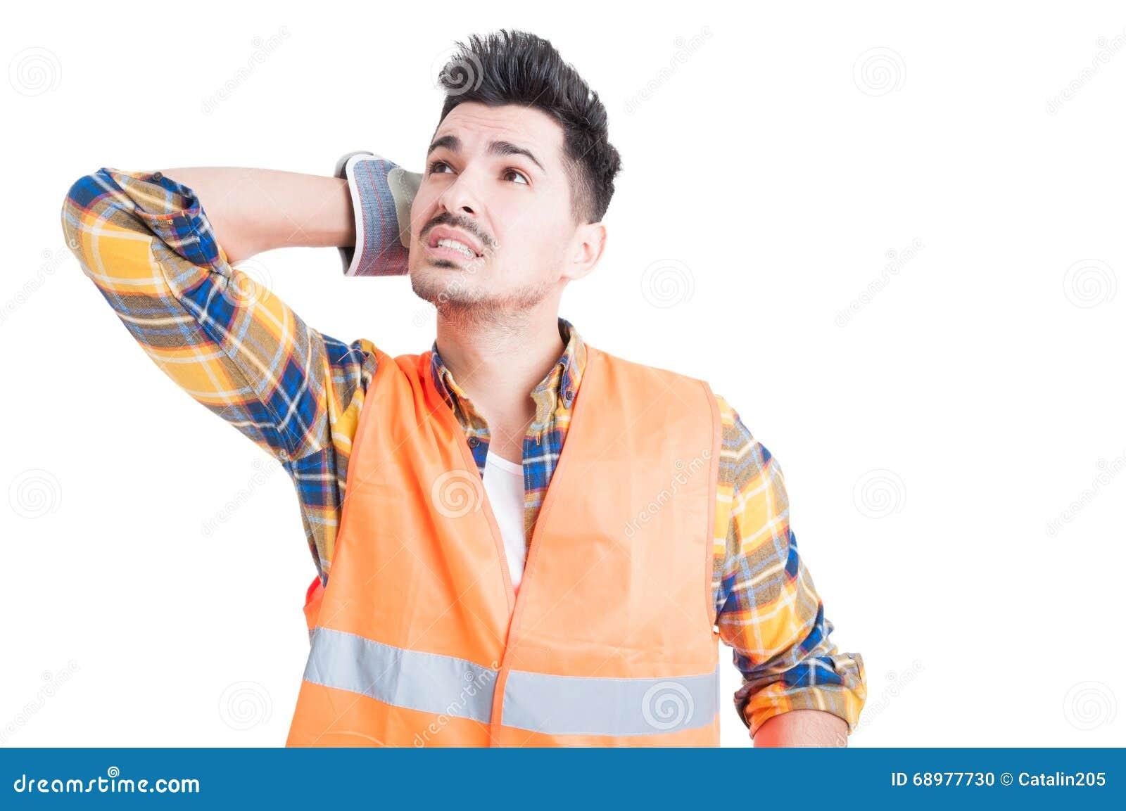 Constructor o ingeniero hermoso en el workwear que parece confundido