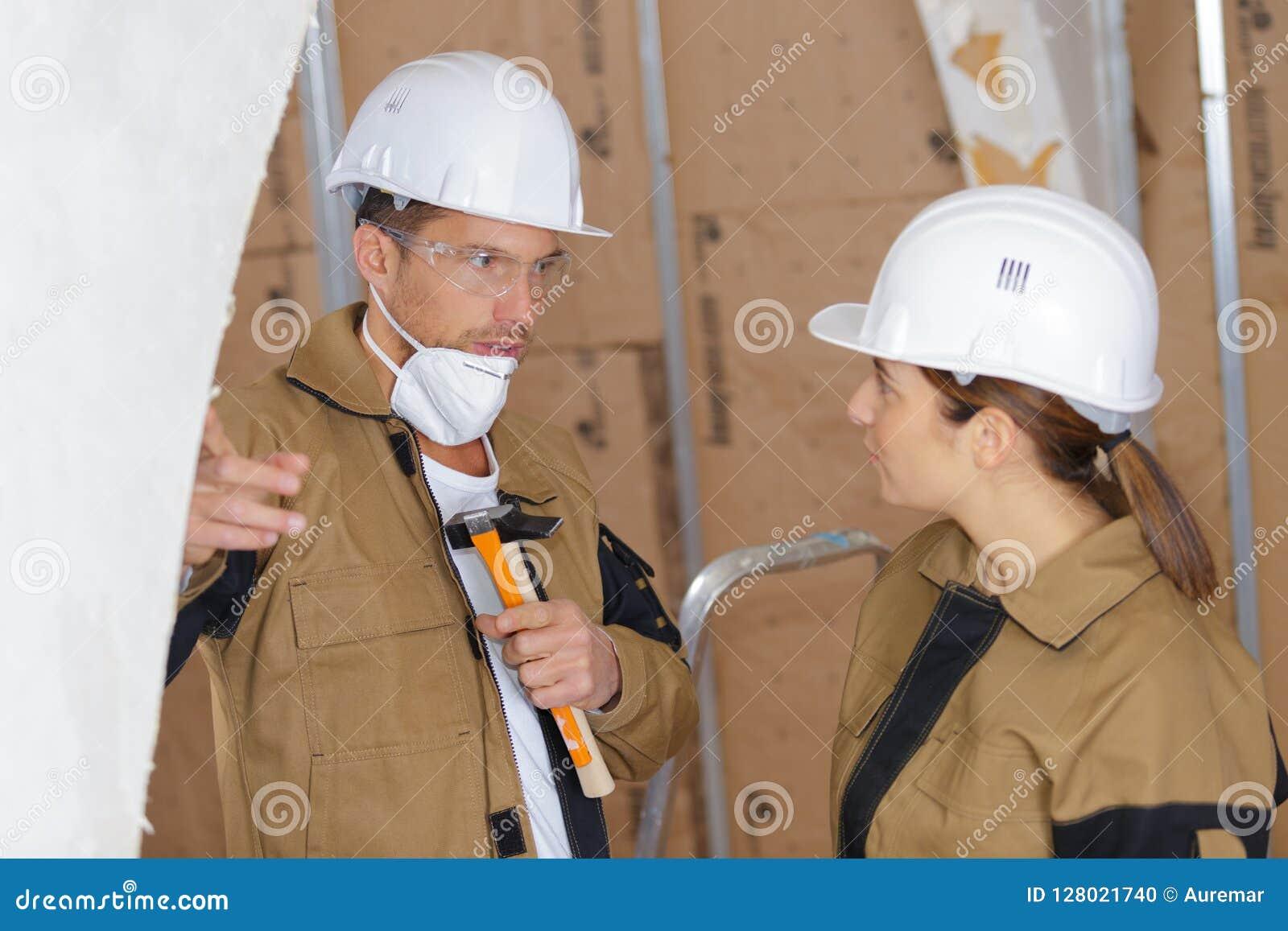 Constructores de sexo masculino y de sexo femenino que hablan en emplazamiento de la obra