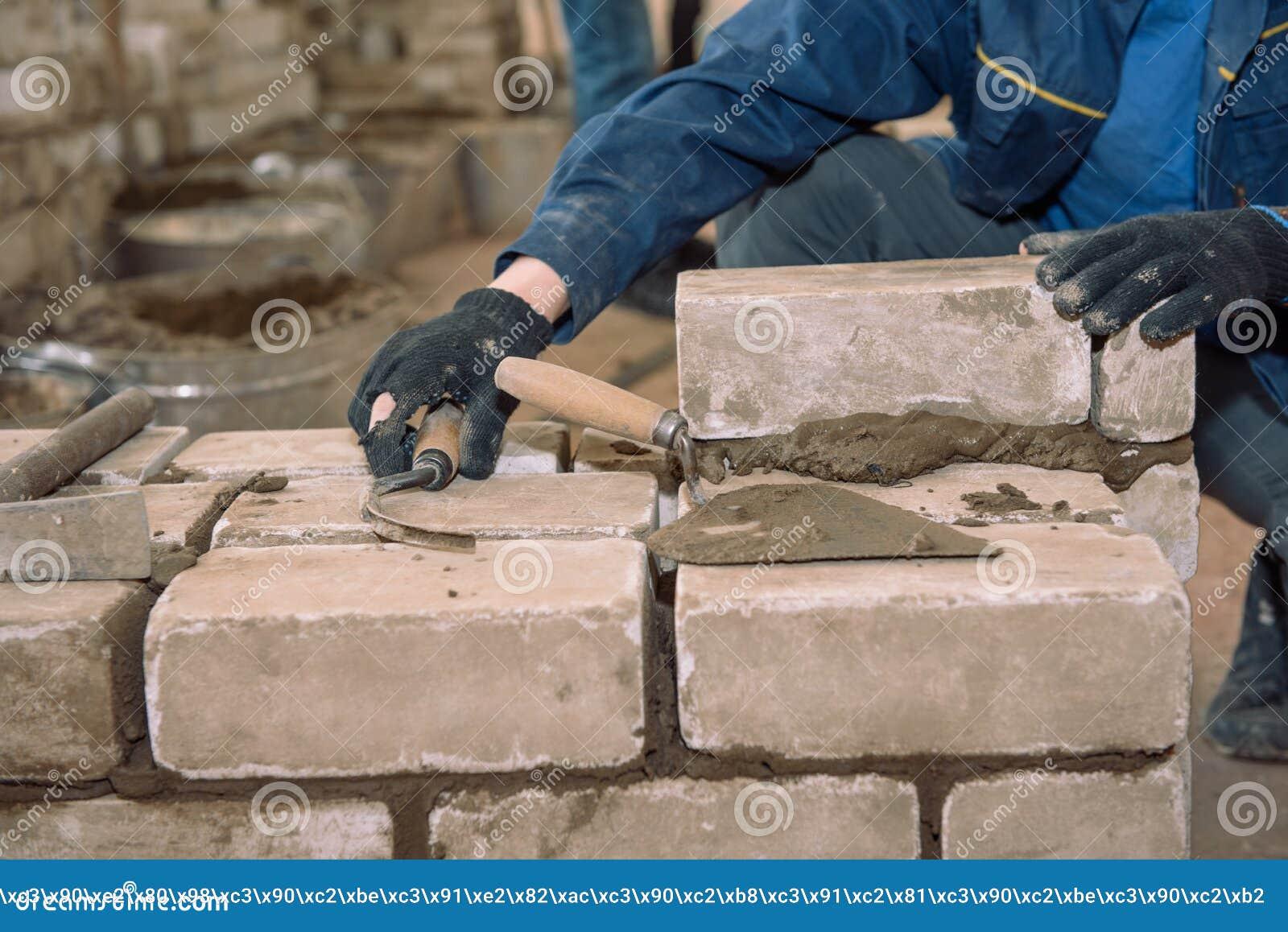 Construisez un mur des briques Les étudiants apprennent à étendre des briques Briques de lien de ciment Ciment tassé par spatule