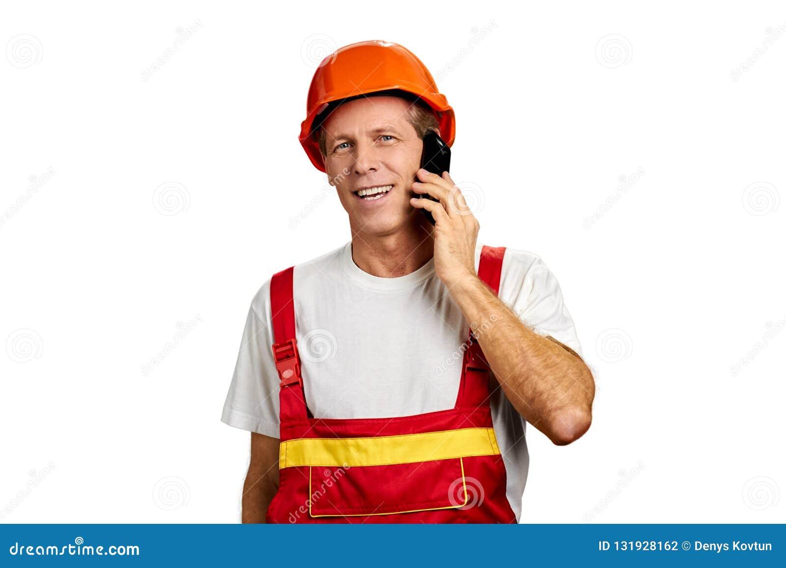 Construtor alegre que fala no telefone celular