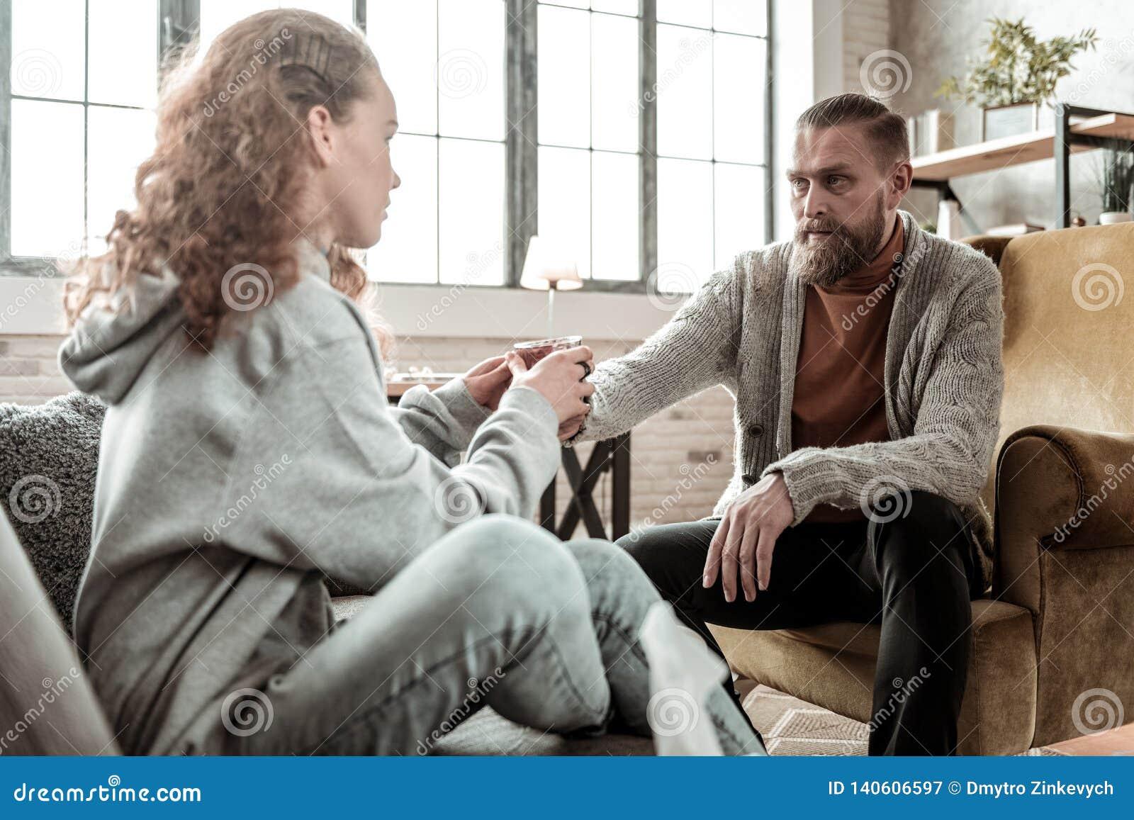 Consulente barbuto che prende cura del suo cliente che dà a ragazza acqua