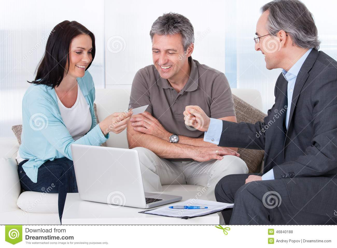 Consultant offering business card to couple