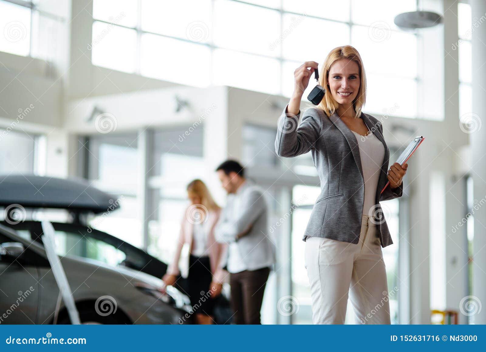 Consultor femenino joven de las ventas del coche que trabaja en la sala de exposici?n