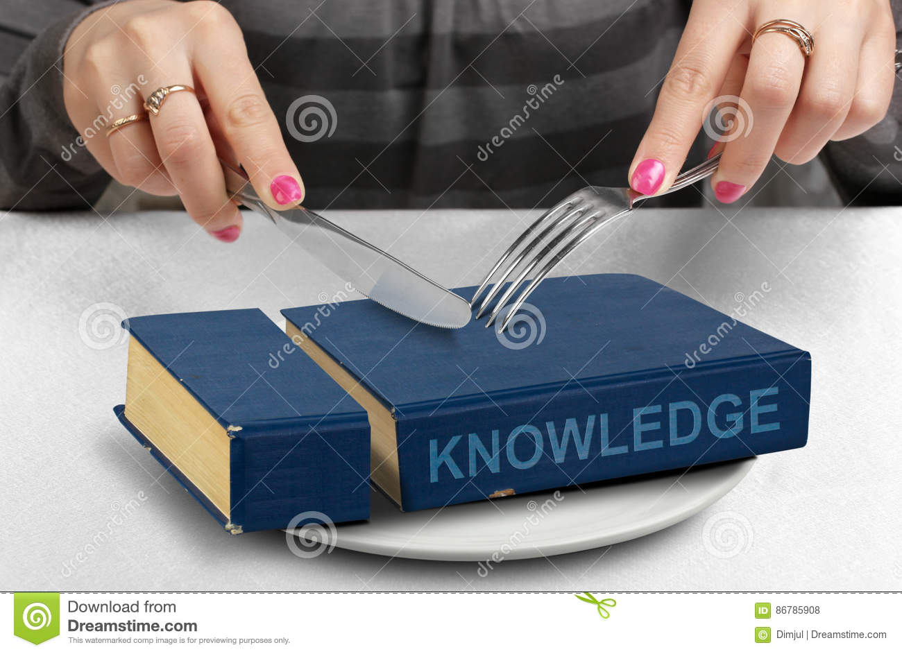 Consume knowledge concept, hands cut book on plate