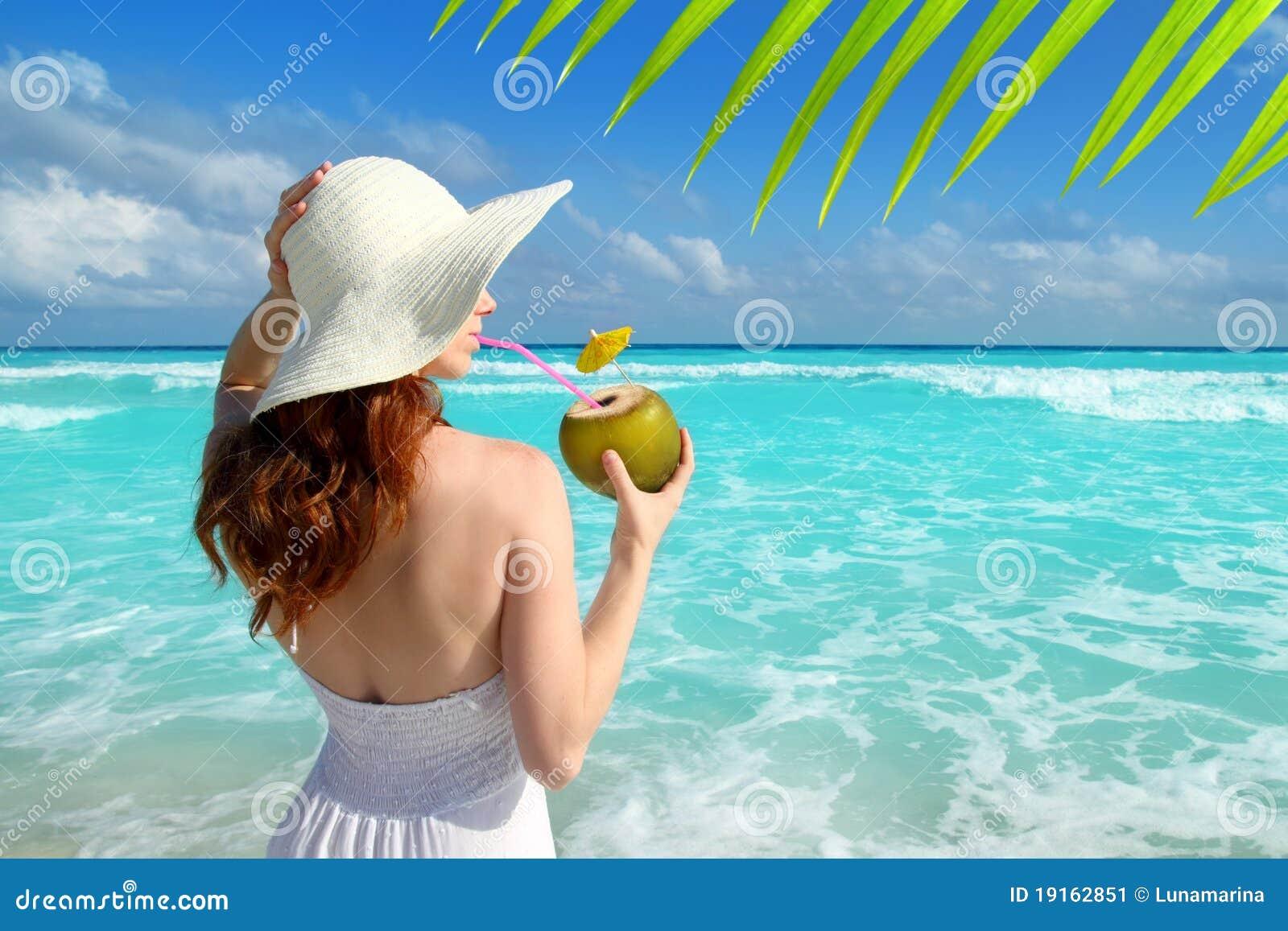 Consumición fresca de la mujer de la playa del coctel del coco