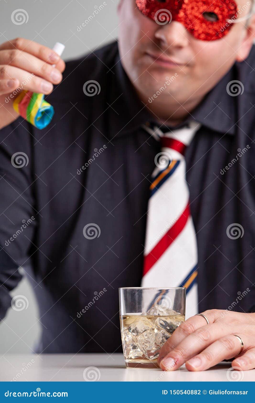 Consumición que se sienta del hombre en el partido que mira un ventilador
