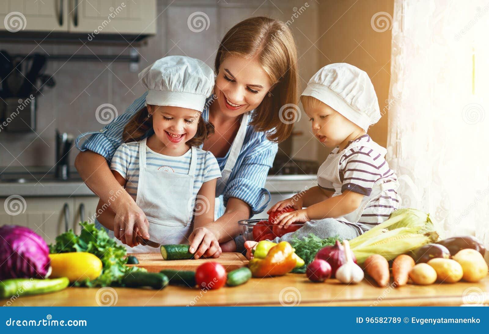 Consumición sana La madre y los niños felices de la familia prepara el veget