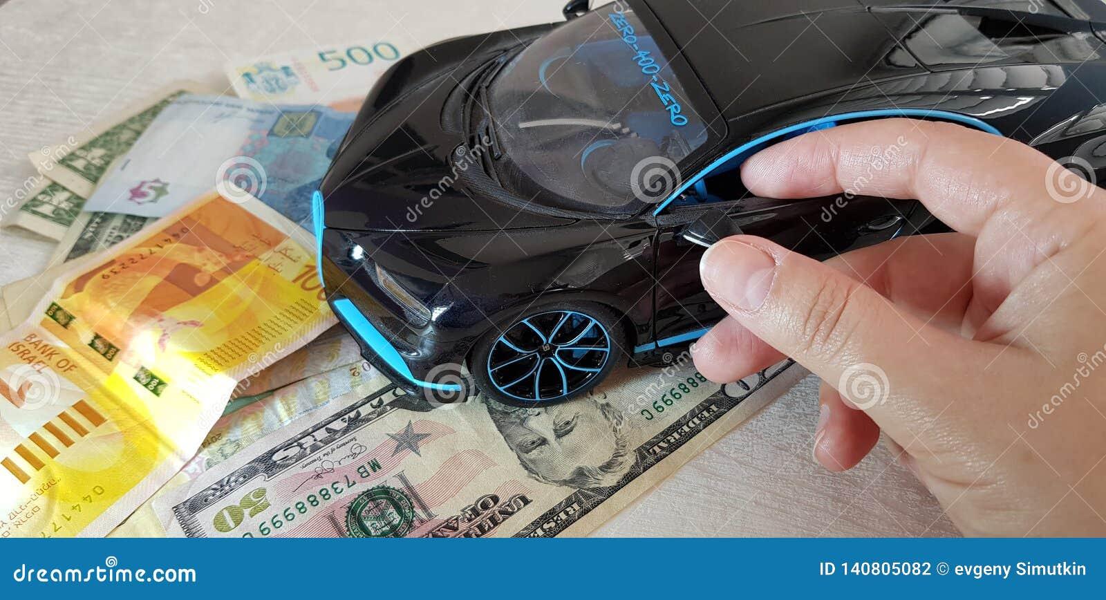 Contacts de jeune fille avec ses doigts un miroir de la position noire de jouet en métal de Bugatti Chiron avec les roues avant s