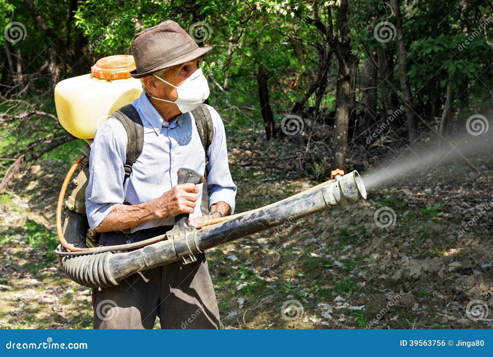 Contadino che spruzza gli alberi con i prodotti chimici