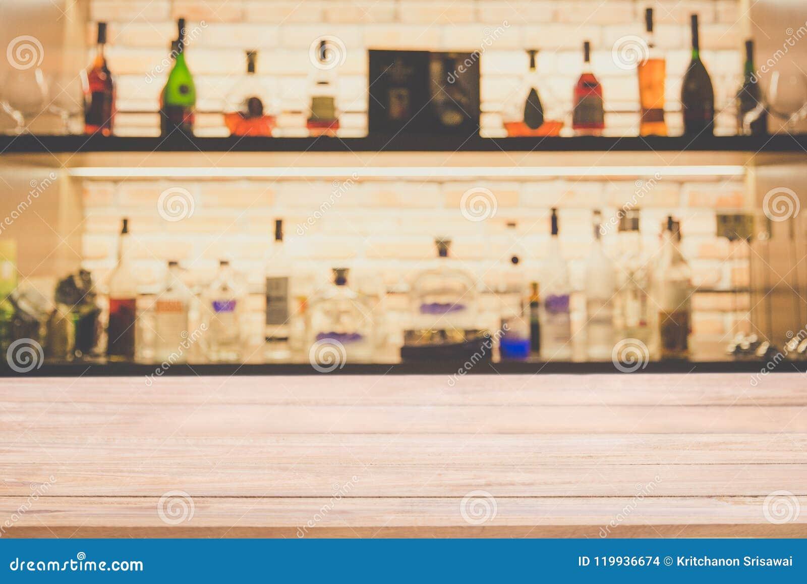 Contador de madeira da barra do pinho vazio com as garrafas do fundo do borrão do re