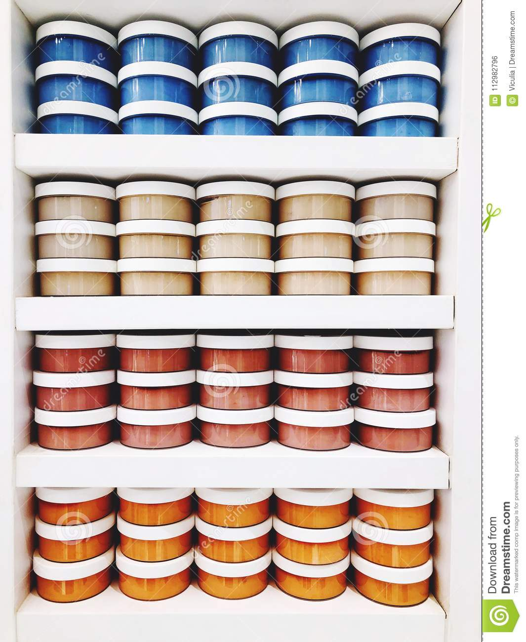 Containers with body scrub on the shelves in the store